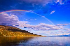 Late Afternoon Rainbow Over Gulf of Corinth Bay, Greece. Dramatic late afternoon light after rainstorm with a colourful rainbow and dark clouds above, and stock photo