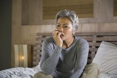 Dramatic lifestyle home portrait of attractive sad and lost middle aged woman with grey hair sitting on bed feeling frustrated. Depressed 40s - 50s mature female stock photos