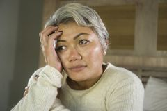 Dramatic lifestyle home portrait of attractive sad and lost middle aged woman with grey hair sitting on bed feeling frustrated. Depressed 40s - 50s mature female stock photo