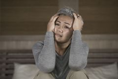Dramatic lifestyle home portrait of attractive sad and lost middle aged woman with grey hair sitting on bed feeling frustrated. Depressed 40s - 50s mature female stock images