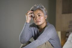 Dramatic lifestyle home portrait of attractive sad and lost middle aged woman with grey hair sitting on bed feeling frustrated. Depressed 40s - 50s mature female royalty free stock photo