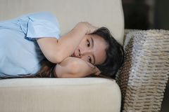 Young beautiful sad and depressed Asian Japanese woman at home sofa couch feeling overwhelmed suffering anxiety crisis and royalty free stock images