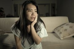 Young beautiful sad and depressed Asian Japanese woman at home sofa couch feeling overwhelmed suffering anxiety crisis and royalty free stock image