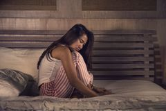 Dramatic lifestyle portrait of young sad and depressed Asian Indonesian woman in pajamas sitting desperate on bed suffering pain. And depression feeling lonely royalty free stock image
