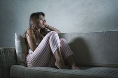 Young sad and depressed Asian Indonesian woman sitting at home couch crying frustrated and upset suffering stress and depression. Dramatic lifestyle portrait of royalty free stock images