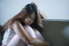 Young sad and depressed Asian Indonesian woman sitting at home couch crying frustrated and upset suffering stress and depression. Dramatic lifestyle portrait of royalty free stock photo