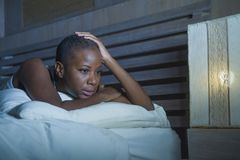 Dramatic lifestyle portrait of young sad and depressed black african American woman on bed sleepless suffering headache insomnia s. Leeping disorder and anxiety stock photography