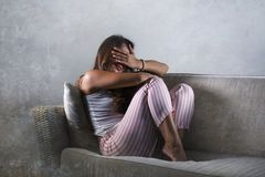 Young sad and depressed woman in pajamas at at home couch crying desperate feeling frustrated and upset suffering stress and. Dramatic lifestyle portrait of royalty free stock photos