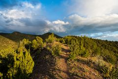 Dramatic light at dusk on a hiking trail through juniper and high hills under a beautiful sky with storm clouds stock photo