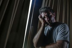 Dramatic light portrait of young sad and depressed attractive man at home looking through room window thoughtful and pensive lost. Dramatic light indoors royalty free stock image