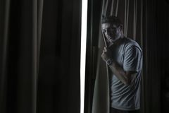 Dramatic light indoors portrait of young sad and depressed attractive man looking through home room window thoughtful and pensive. In pain suffering depression stock image