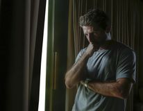 Dramatic light indoors portrait of young sad and depressed attractive man looking through home room window thoughtful and pensive. In pain suffering depression royalty free stock image