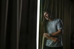 Dramatic light indoors portrait of young sad and depressed attractive man looking through home room window thoughtful and pensive. In pain suffering depression royalty free stock images