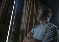 Dramatic light indoors portrait of young sad and depressed attractive man looking through home room window thoughtful and pensive. In pain suffering depression stock photography