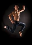 Dramatic light photo of modern acrobat jumping Stock Photo