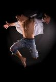 Dramatic light photo of modern acrobat jumping. In front of black background stock photo