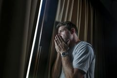 Dramatic light portrait of young sad and depressed attractive man at home looking through room window thoughtful and pensive lost. Dramatic light indoors royalty free stock photography