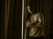Dramatic light portrait of young sad and depressed attractive man at home looking through room window thoughtful and pensive lost. Dramatic light indoors stock photos