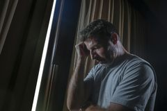 Dramatic light portrait of young sad and depressed attractive man at home looking through room window thoughtful and pensive lost. Dramatic light indoors royalty free stock photo