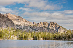 Dramatic lighting on jagged mountain peaks with lake Stock Photos