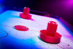 Dramatic lit air hockey table with puck and paddles