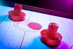 Dramatic lit air hockey table with puck and paddles Stock Image