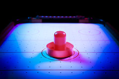 Dramatic lit air hockey table with puck and paddles Royalty Free Stock Photo