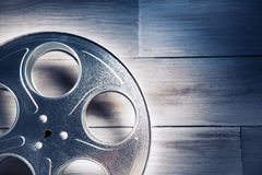 Dramatic lit image of a movie reel. Movie reel on a wooden background royalty free stock photos