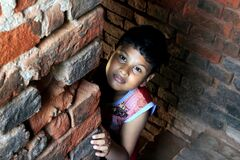 Dramatic look of a child. Portrait of a child. A child is playing Hide-and-seek on the top of the stairs.