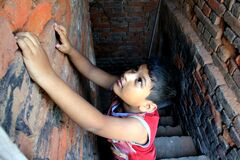 Dramatic look of a child. Portrait of a child. A child is trying to climb up on the wall.