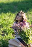 Dramatic looking young girl holding lavender bouquet at the field royalty free stock images