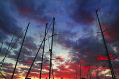 Dramatic marina sailboat mast sunset sky backlight Royalty Free Stock Images