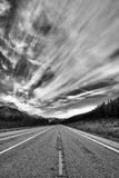 Dramatic Monochrome Road. Monochrome landscape of a mountain road with a dramatic sky Stock Photos