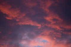 Dramatic and moody pink, purple, blue cloudy sunset sky Stock Photos