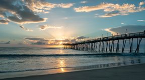 Dramatic sunrise lights up the clouds and sunbeams burst from the clouds. An old wooden ocean pier at sunrise. stock image