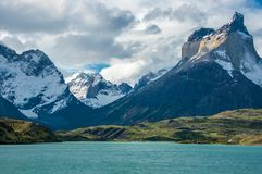 Soaring Cuernos del Paine across turquoise Grey Lake, Chile. Dramatic mountains - the Cuernos del Paine - soar skyward with their rocky peaks and glaciers above royalty free stock image