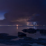 Dramatic nature background - thunders in dark sky over the sea Stock Photos