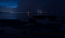 Dramatic nature background - thunders in dark sky over the sea Stock Photography