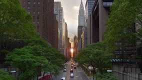 Dramatic New York City Manhattanhenge Sunset Effect. A cinematic wide evening establishing shot over 42nd Street in New York City during Manhattanhenge stock video footage