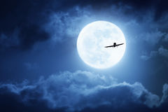 Dramatic Nighttime Sky With Large Full Blue Moon and Commercial Aircraft. Dramatic photo illustration of a nighttime sky with brightly lit clouds and large, full stock image