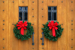 Dramatic oak wooden church doors. Gothic oak wooden church doors with ornate metal hardware and wreaths royalty free stock photo