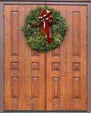 Dramatic oak wooden church doors. Gothic oak wooden church doors with wreath with red bow Royalty Free Stock Images