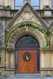 Dramatic oak wooden church doors. Gothic oak wooden church doors with wreath with red bow Royalty Free Stock Image
