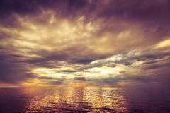 Dramatic ocean sunset. With stormy clouds rain and sun rays royalty free stock photography