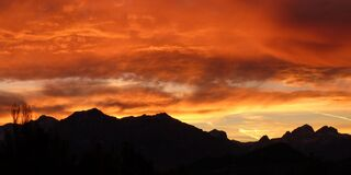 Dramatic orange sunrise over mountains stock image