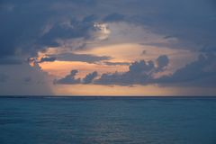 Dramatic orange sunrise sky with clouds over blue peaceful ocean of maldives stock photography