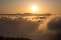 Dramatic orange sunset above the fog Stock Image