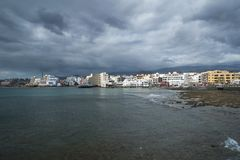 Dramatic overcast sky, low tide and calm waves in the town side of El Medano, Tenerife, Canary Islands, Spain. Horizontal shot of the scenic El Madano town from Royalty Free Stock Image