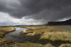 Dramatic panorama of a river in the South of Iceland. Horizontal panorama view of an Icelandic river running through the grass with rain stormy clouds above and Royalty Free Stock Images