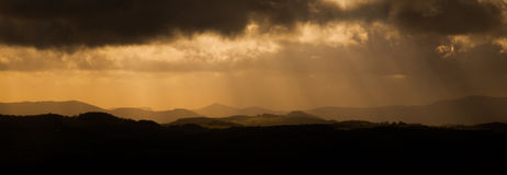 Dramatic panorama - sun beams bursting through dark stormy clouds Stock Image